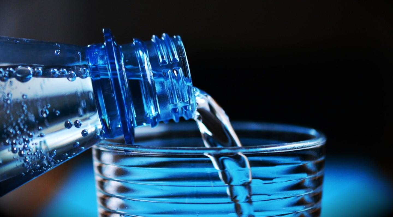 bottiglia che riempie un bicchiere di vetro